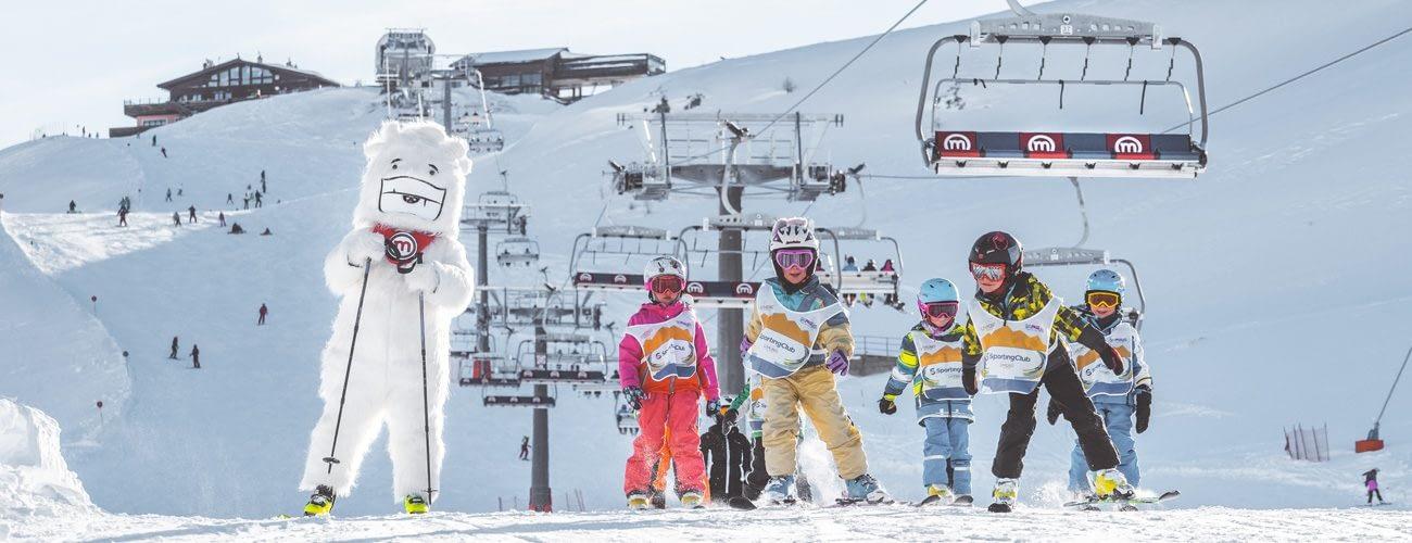 Bambini che sciano insieme a Yepi sulla pista blu della ski area Mottolino a Livigno