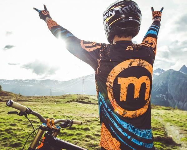 Biker che guarda l'orizzonte esultando al Mottolino Bikepark di Livigno