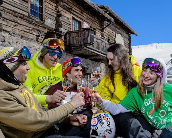Gruppo di amici brinda al Camanel di Planon sulla ski area Mottolino a Livigno