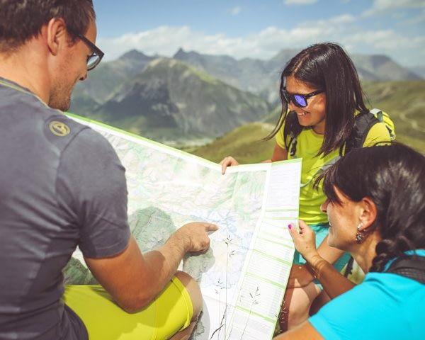 Gruppo che osserva la mappa prima di mettersi in viaggio sui sentieri di Livigno a piedi
