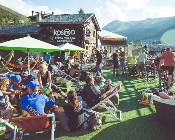 Relax dei bikers sulla terrazza esterna del Kosmo nella stagione estiva di Mottolino a Livigno